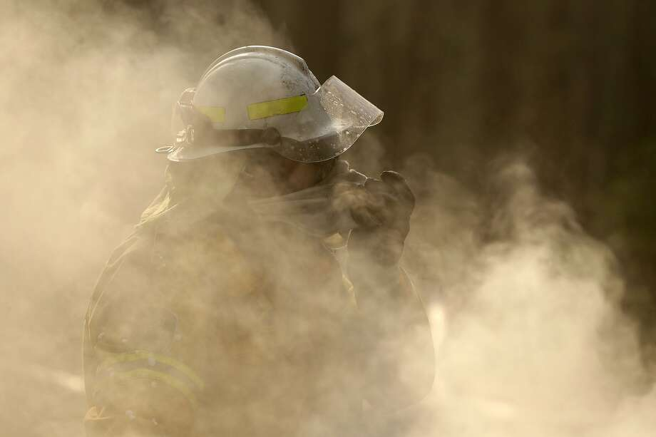 A firefighter covers his face as he battles a wildfire near Bendalong, Australia. Residents andh ealth professionals are worried about the long-term impact from such smoke exposure. Photo: Rick Rycroft / Associated Press