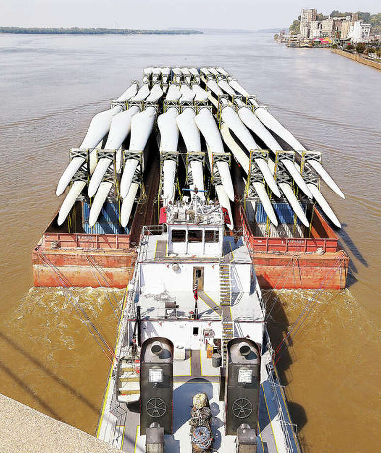 A towboat pushes three barges, loaded with what appear to be 54 blades for wind turbines, under the Clark Bridge in Alton on their way up river. Photo: John Badman | The Telegraph