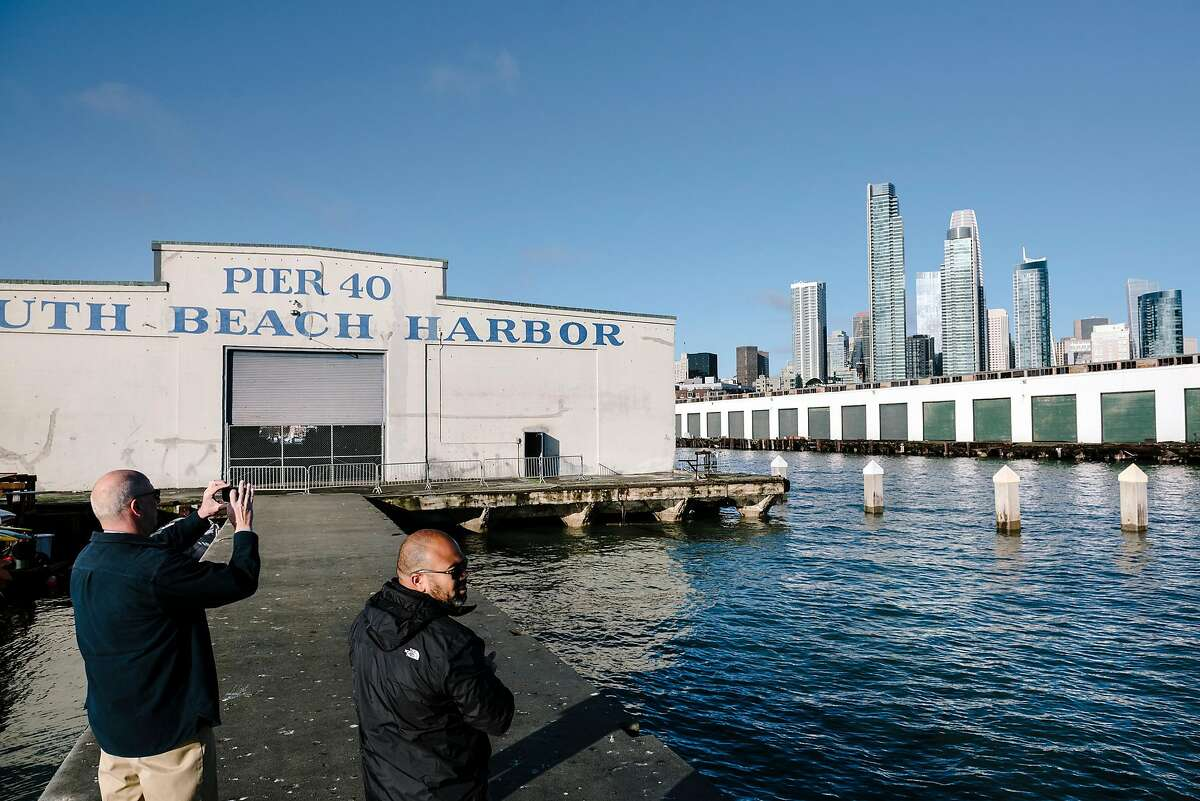 The Port of San Francisco's senior waterfront planner, David Beaupre, left, and communications director, Randy Quezada, take photos of the water facing sides of piers 40 and 38, in San Francisco, California, Thursday, January 9th, 2020. The Port of San Francisco is seeking new proposal ideas for Piers 38 and 40 that could include offices, retail, maritime and public uses.