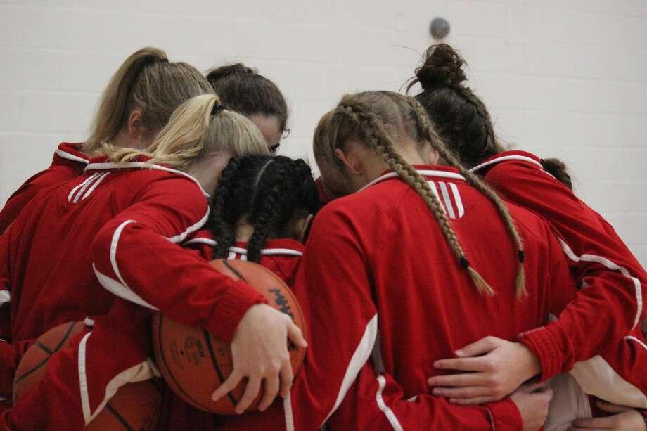 Benzie Central's varsity girls basketball team huddles before taking the court in their season opener back in December. Photo: Robert Myers