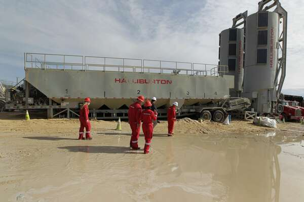Halliburton's employees walk by a Sandcastle at a fracking site Monday, June 26, 2017, in Midland. ( Steve Gonzales / Houston Chronicle )