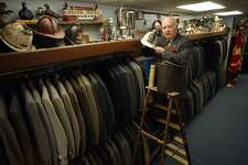 """Ansonia, Connecticut-2/20/03: Recipient of the Dr. John I. Howe Award by the Derby Historical Society,Charles Seccombe, owner of Seccombe's Men's Shop, is the """"caretaker"""" of historical and antique items that was either given to him by donors or personal collection in his clothing store. The award honors his attempts at preserving local history. Heholds the circa1877 Ansonia Fire Dept. helmet that belonged to second assistant fire chief Arthur Bartholomew who was also the first mayor of Ansonia, a leather fire brigade bucket and an antique fire extinquisher. ©2003 Peter Hvizdak ph0082c #2103"""