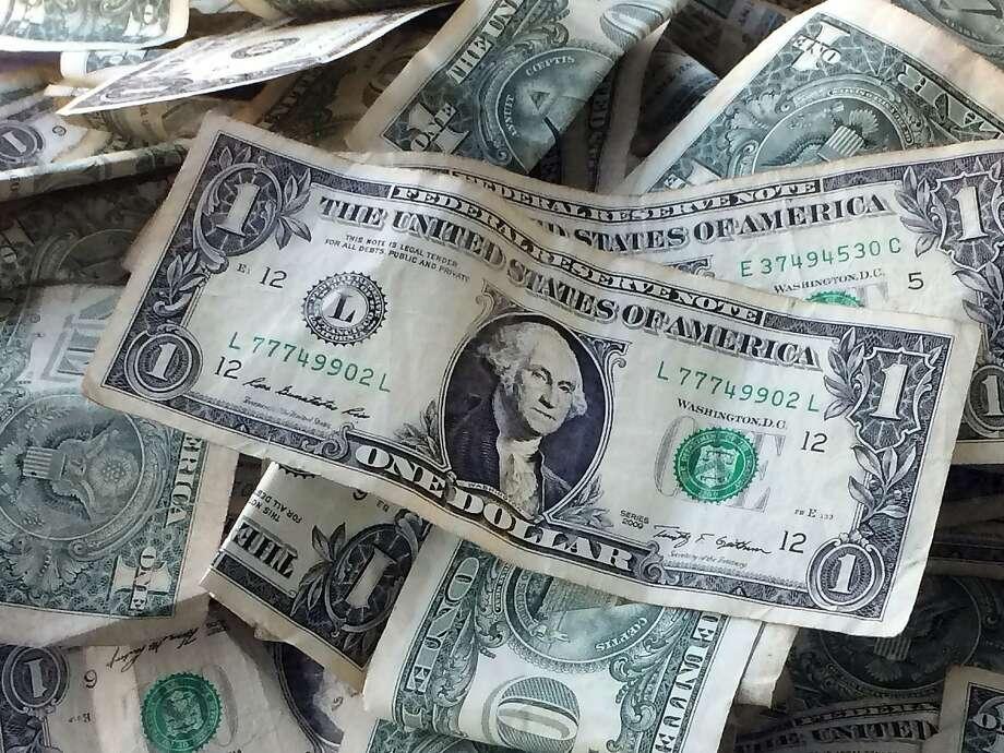 FILE - This Oct. 24, 2016 file photo shows dollar bills in New York. (AP Photo/Mark Lennihan, File) Photo: Mark Lennihan, Associated Press