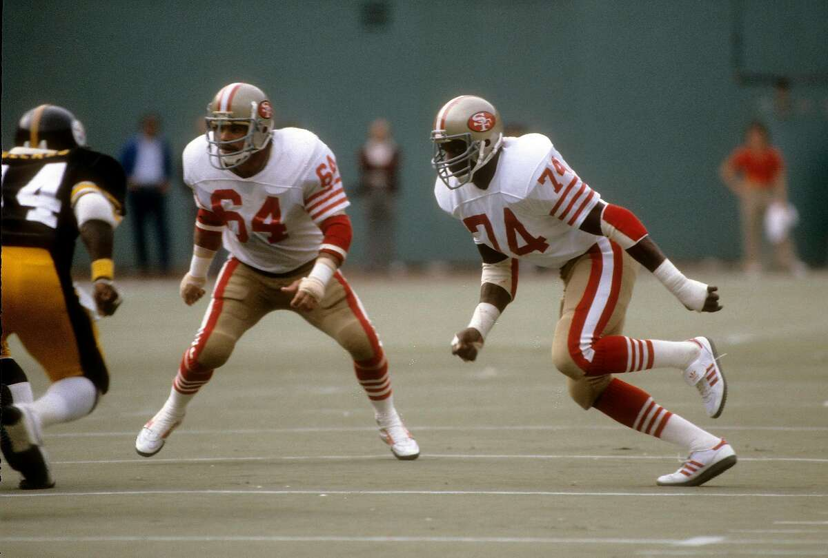 PITTSBURGH, PA - NOVEMBER 1: Defensive end Fred Dean #74 of the San Francisco 49ers pursues the play with linebacker Jack Reynolds #64 against the Pittsburgh Steelers during an NFL football game November 1, 1981 at Three Rivers Stadium in Pittsburgh, Penn