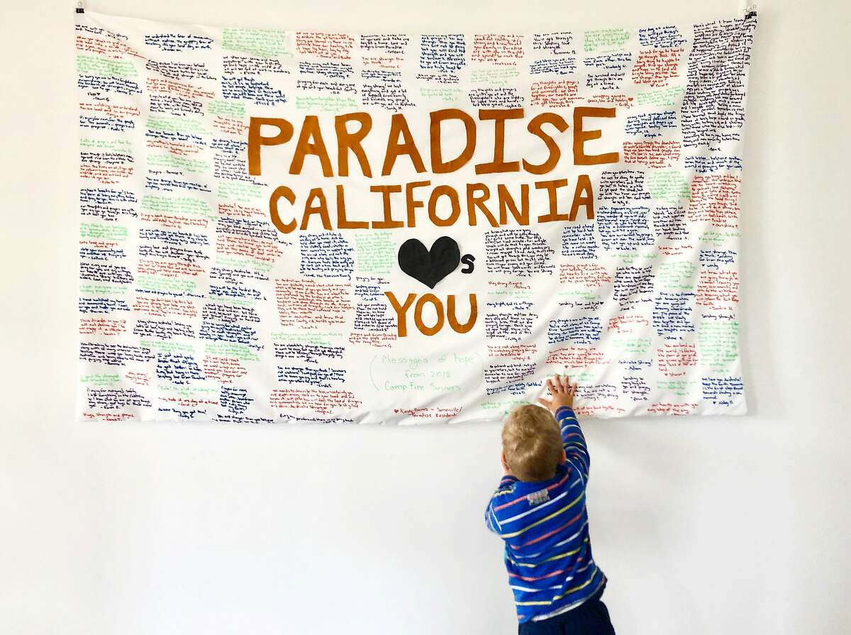 In this undated photo provided by Kasey Baines, a child touches a banner with supportive messages from survivors of a wildfire known as the 2018 Camp Fire in Paradise, Calif., for people evacuating bush fires in Australia. Baines, an American living in Australia who has endured wildfires on both continents is sharing heartfelt messages of hope and advice for those who have fled their homes Down Under. (Kasey Baines via AP)