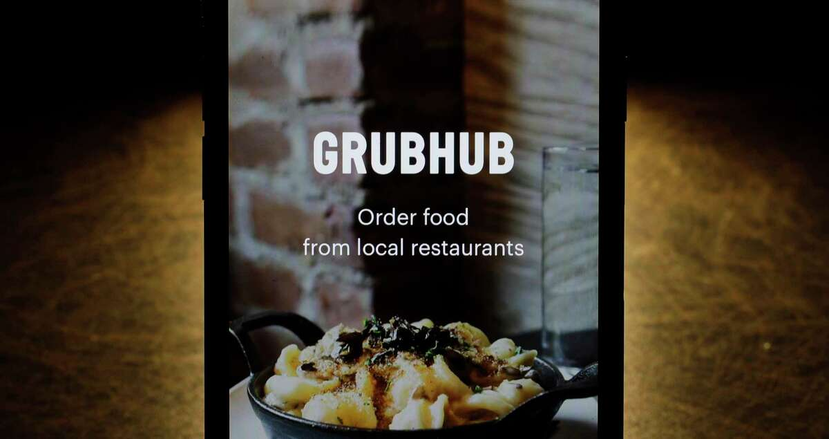 FILE - This Feb. 20, 2018, file photo shows the Grubhub app on an iPhone in Chicago. Albany County Executive Dan McCoy announced an executive order Dec. 28, 2020 to further cap fees that food delivery companies have been adding McCoy said that is gauging restaurant profits. (AP Photo/Charles Rex Arbogast, File)