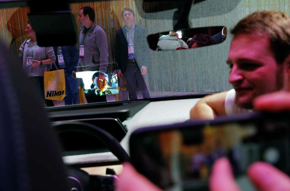 Attendees crowd around a display showing Audi's 3D mixed-reality head-up display in the Audi booth at the CES tech show, Wednesday, Jan. 8, 2020, in Las Vegas. (AP Photo/John Locher)