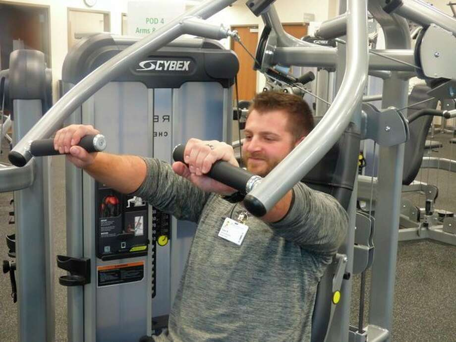 Staff demonstrate workout equipment at theManistee Health and Fitness center. (Scott Fraley/News Advocate)