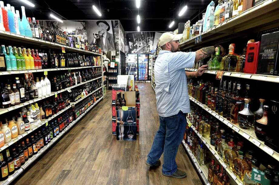Longhorn Liquor employee Shawn McNulty organizes shelves at the Beaumont Dowlen Road location Friday. Owner Dennis Williams has two new Houston stores opening this spring and has plans for future Southeast Texas stores, as well. The expansion is part of Williams' business goal of opening two new stores a year. Photo taken Friday, January 3, 2020 Kim Brent/The Enterprise Photo: Kim Brent / The Enterprise / BEN