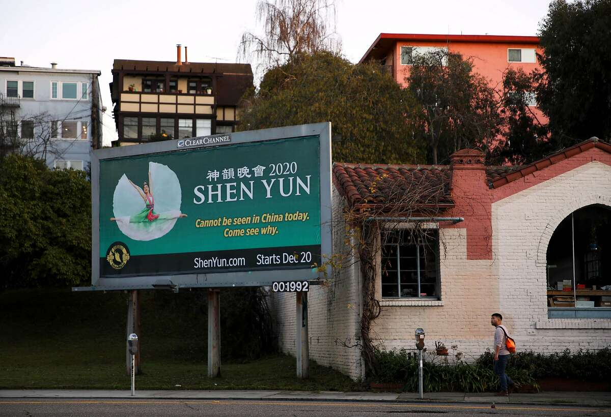 A man walks near a Shen Yun billboard as he approaches Park Blvd. and East 20th Street, in Oakland, Calif., on Tuesday, January 7, 2020.