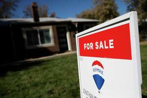FILE - In this Oct. 22, 2019 file photo, a sign stands outside a home for sale in southeast Denver.  U.S. long-term mortgage rates were little changed this week of Dec. 23, remaining at historically low levels to prod prospective homebuyers.   (AP Photo/David Zalubowski, File)