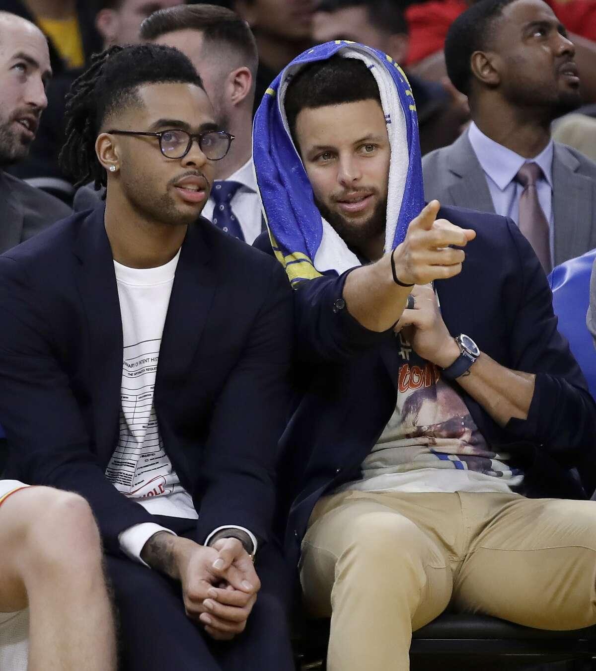 Golden State Warriors' Stephen Curry, right, gestures while speaking to teammate D'Angelo Russell on the bench as they watch during the second half of the team's NBA basketball game against the Milwaukee Bucks in January. The team still wants to see how the two will play together once Curry returns to the court.