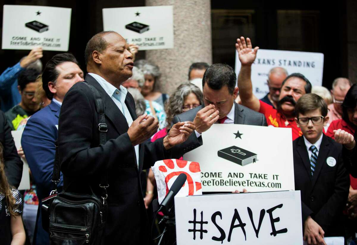 """Dallas Pastor Stephen Broden leads a closing prayer during a press conference as part of """"Save Chick-Fil-A Day"""" at the Texas state capital extension in April 2019 in Austin. A lawsuit filed against San Antonio in support of Chick-fil-A will be allowed to proceed, a judge ruled Thursday."""