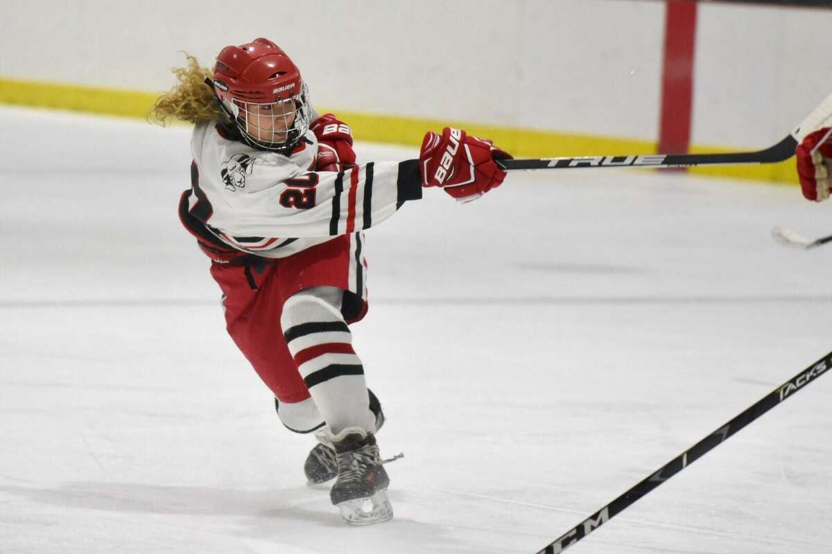 New Canaan's Quincy Connell (20) follows through on a shot during a girls ice hockey game against Greenwich at the Darien Ice House on Thursday.