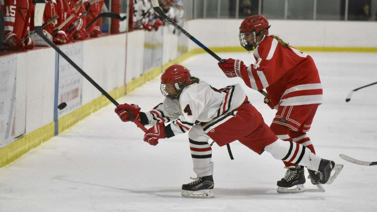 New Canaan's Kaleigh Harden (4) and Greenwich's Elizabeth Anderson battle for the puck during Thursday's game at the Darien Ice House.