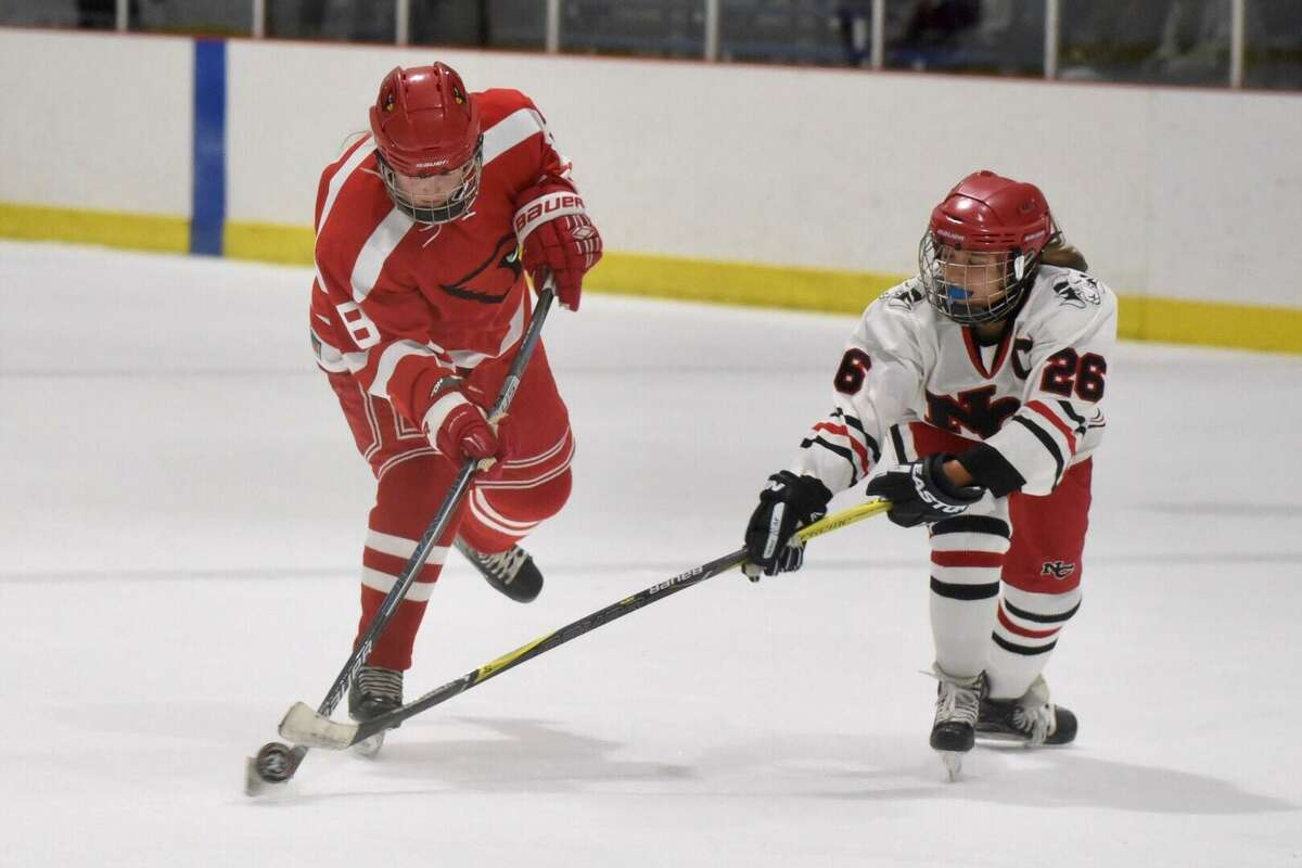Greenwich's Lexi Danielson (8) takes a shot while New Canaan's Sophie Potter defends during their game at he Darien Ice House on Thursday.