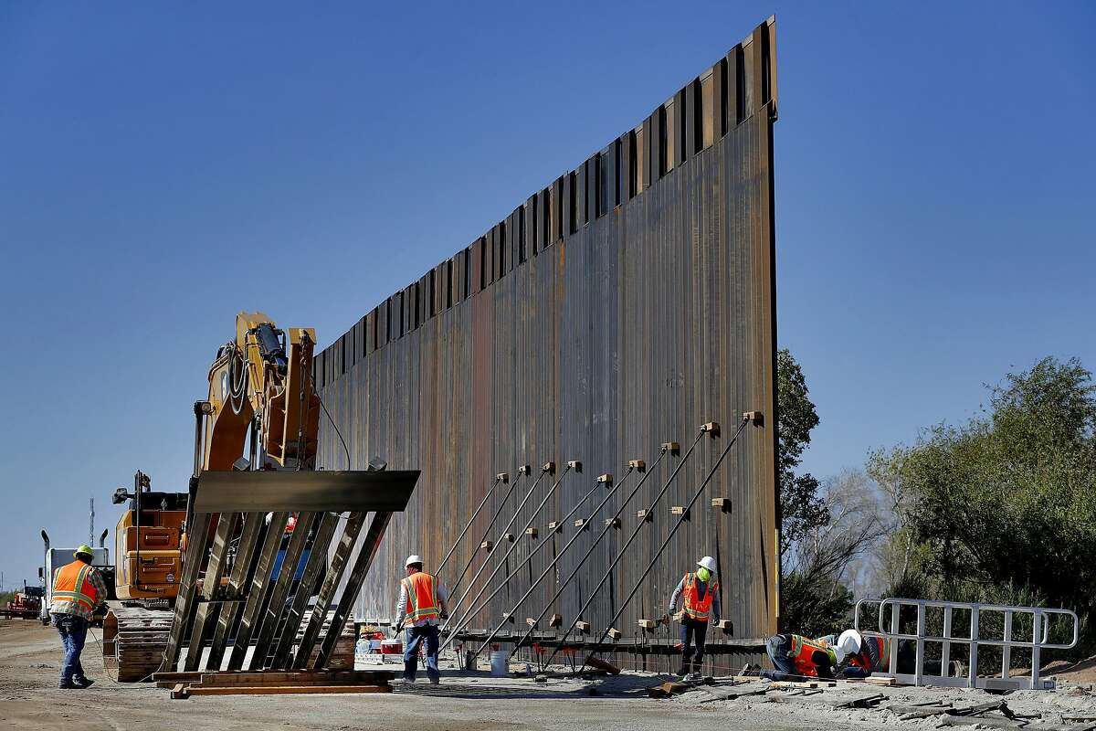 FILE - In this Sept. 10, 2019 file photo, government contractors erect a section of Pentagon-funded border wall along the Colorado River in Yuma, Ariz. The White House says construction of the U.S.-Mexico border wall will move forward after a federal appeals court ruling that frees up construction money. The 2-1 ruling on Wednesday halted a federal judge's ruling in December that had prevented the government from spending $3.6 billion diverted from 127 military construction projects to pay for 175 miles of border wall. (AP Photo/Matt York)