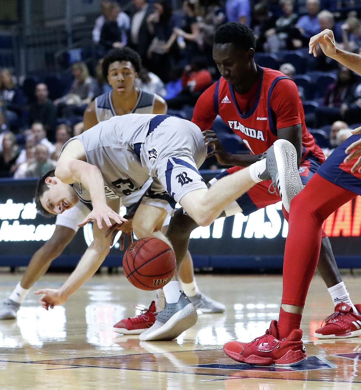 Rice Owls guard Drew Peterson (23) stumbles as he tries to stay in control of the ball against Florida Atlantic Owls forward Madiaw Niang (1) during the first half of an NCAA men's college basketball game at Tudor Fieldhouse Thursday, Jan. 9, 2020, in Houston.