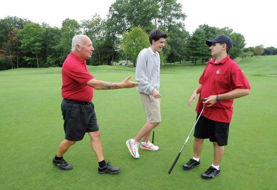 Volunteer Angelo Pellettiere reaches out to shake Frank Rigos' hand as volunteer Jay Alter walks off the green during the Challenged People In Motion golf tournament at Sterling Farms Golf Course in Stamford, Conn. on Thursday August 12, 2010. Photo: Kathleen O'Rourke / Stamford Advocate