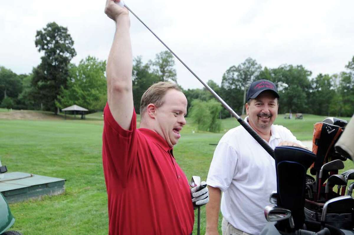 Volunteer Ralph D'Agostino assists Christopher Backiel during the Challenged People In Motion golf tournament at Sterling Farms Golf Course in Stamford, Conn. on Thursday August 12, 2010.