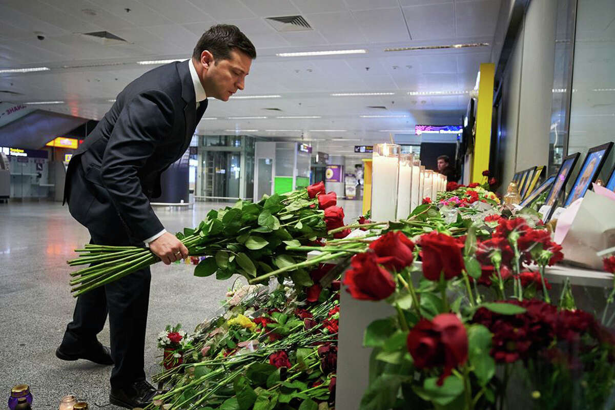 This handout picture taken and released by the Ukrainian presidential press service shows Ukraine's President Volodymyr Zelensky placing flowers at a memorial for the victims of the Ukraine International Airlines Boeing 737-800 crash in the Iranian capital Tehran, at the Boryspil airport outside Kiev on January 9, 2020. - A Ukrainian airliner crashed shortly after take-off from Tehran on January 8, 2020 killing all 176 people on board, mainly Iranians and Canadians. (Photo by HO / UKRAINIAN PRESIDENTIAL PRESS SERVICE / AFP) / RESTRICTED TO EDITORIAL USE - MANDATORY CREDIT