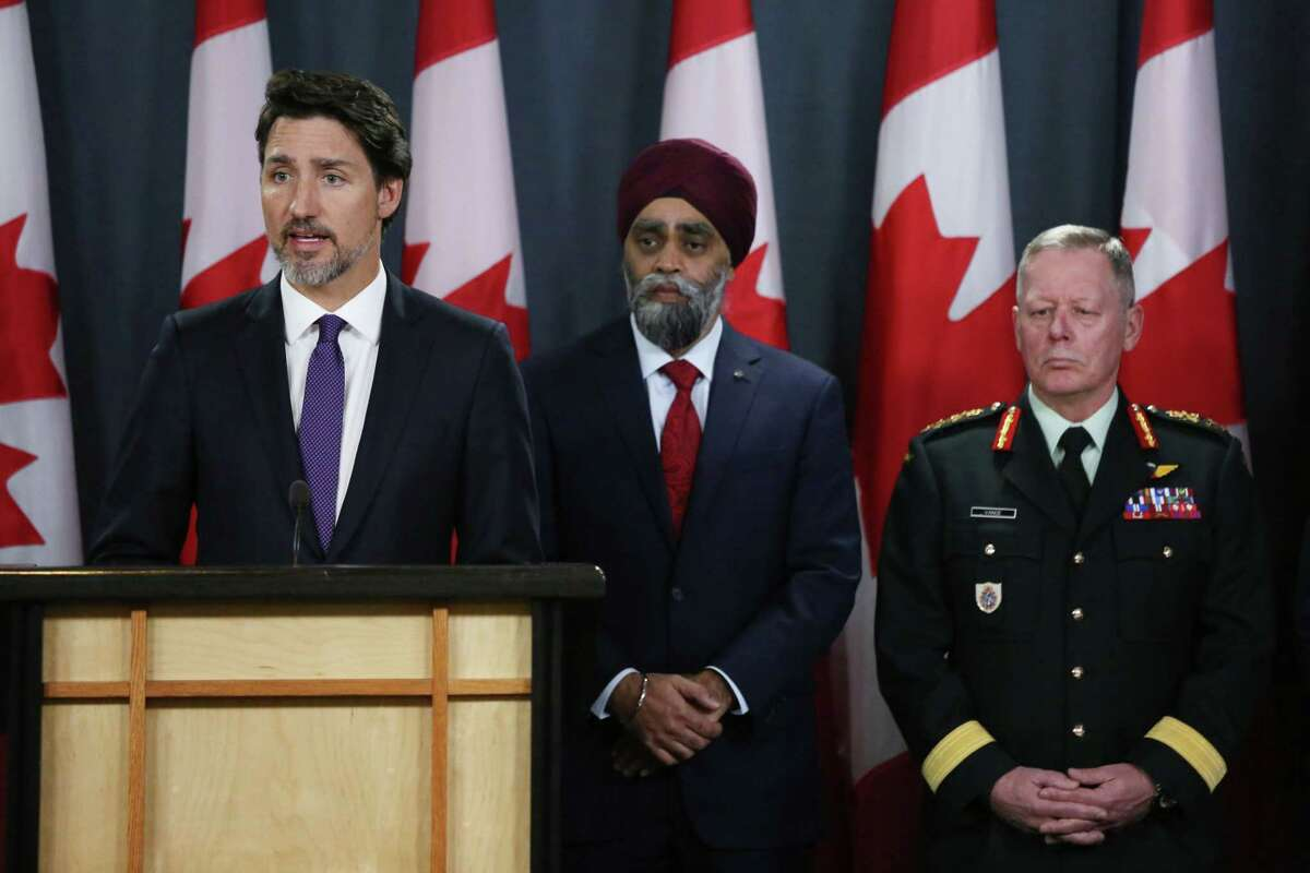 Minister of National Denfence Harjit Sajjan (C) and Chief of Defence Staff General Jonathan Vance (R) listen as Canadian Prime Minister Justin Trudeau (L) speaks during a news conference January 9, 2020 in Ottawa, Canada. - Prime Minister Justin Trudeau said Thursday that Canada had intelligence from multiple sources indicating that a Ukrainian airliner which crashed outside Tehran was mistakenly shot down by Iran. (Photo by Dave Chan / AFP) (Photo by DAVE CHAN/AFP via Getty Images)