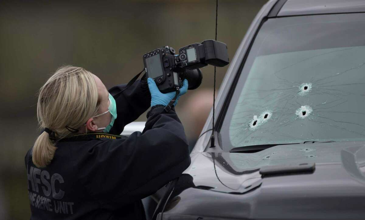 Houston Forensic Science Center investigators work on an officer-involved shooting where a Houston Police Department officer discharged his weapon from inside a police truck at a suspect on foot at the 8000 block of Martin Luther King Boulevard on Thursday, Jan. 9, 2020, in Houston.