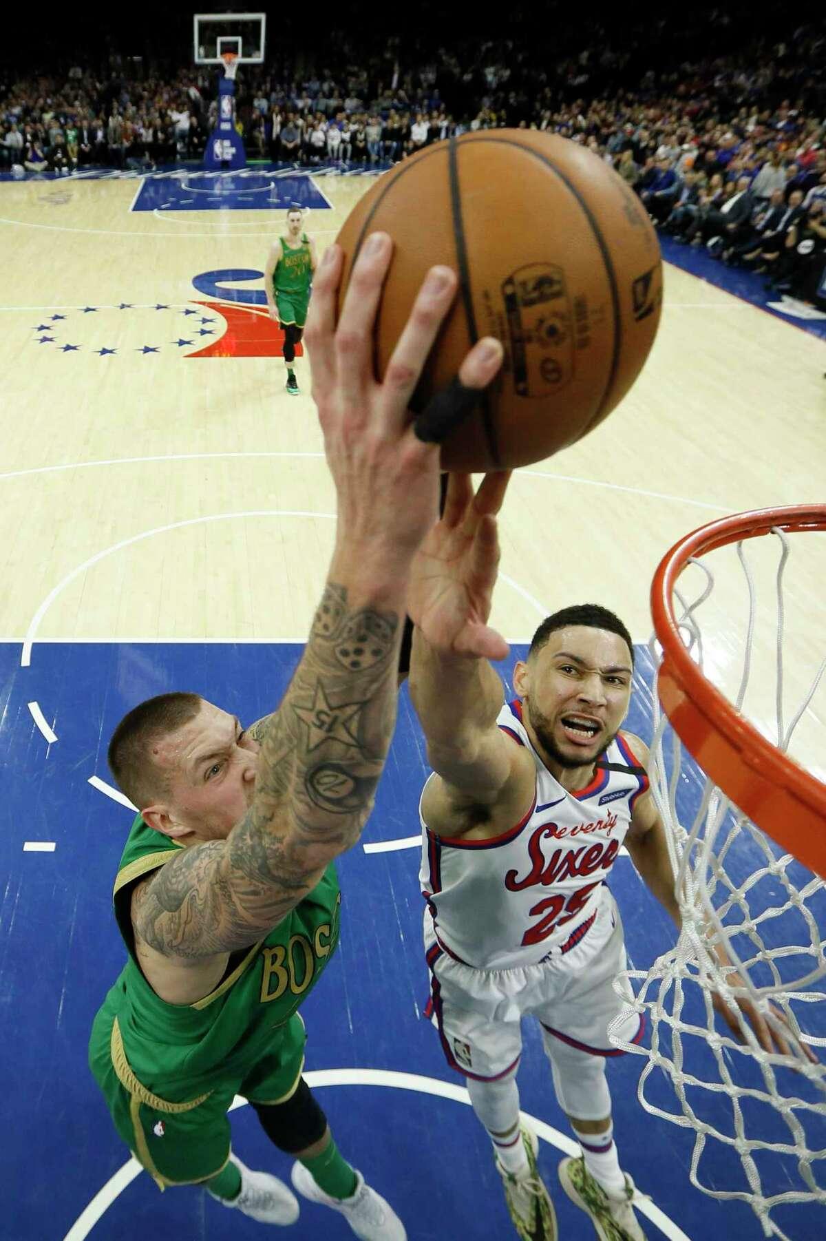 Boston Celtics' Daniel Theis, left, goes up to dunk against Philadelphia 76ers' Ben Simmons during the first half of an NBA basketball game, Thursday, Jan. 9, 2020, in Philadelphia. (AP Photo/Matt Slocum)