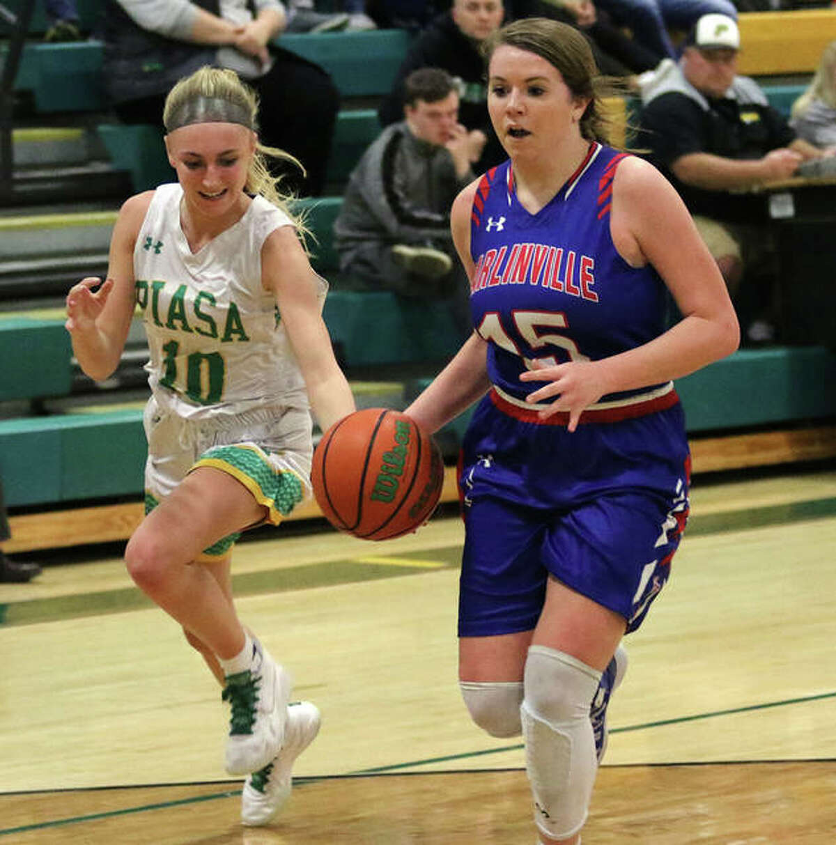 Southwestern's Morgan Durham (left) knocks the ball away from and off of Carlinville's Gracie Reels to force a turnover on a fastbreak in the first half of a South Central Conference girls basketball game Thursday night in Piasa.
