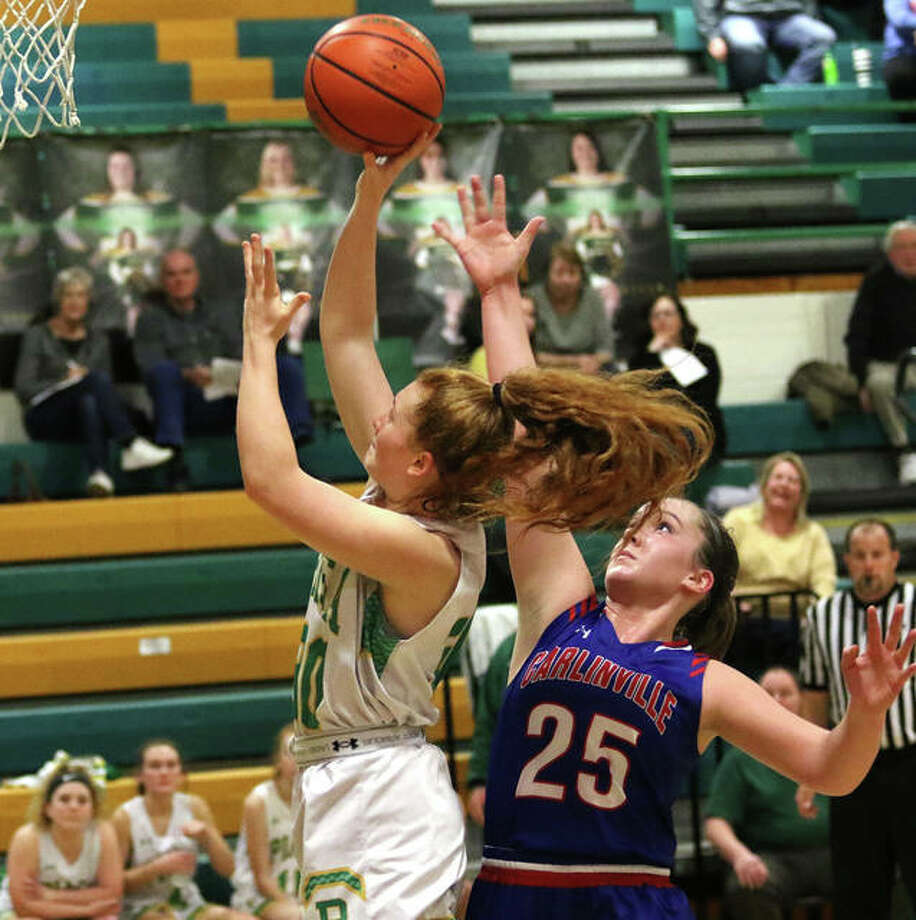 Southwestern's Rylee Smith (left) gets past Carlinville's Sarah DeNeve and scores points that give the Piasa Birds a 21-19 third-quarter lead they would not relinquish Thursday night in Piasa. Photo: Greg Shashack / The Telegraph