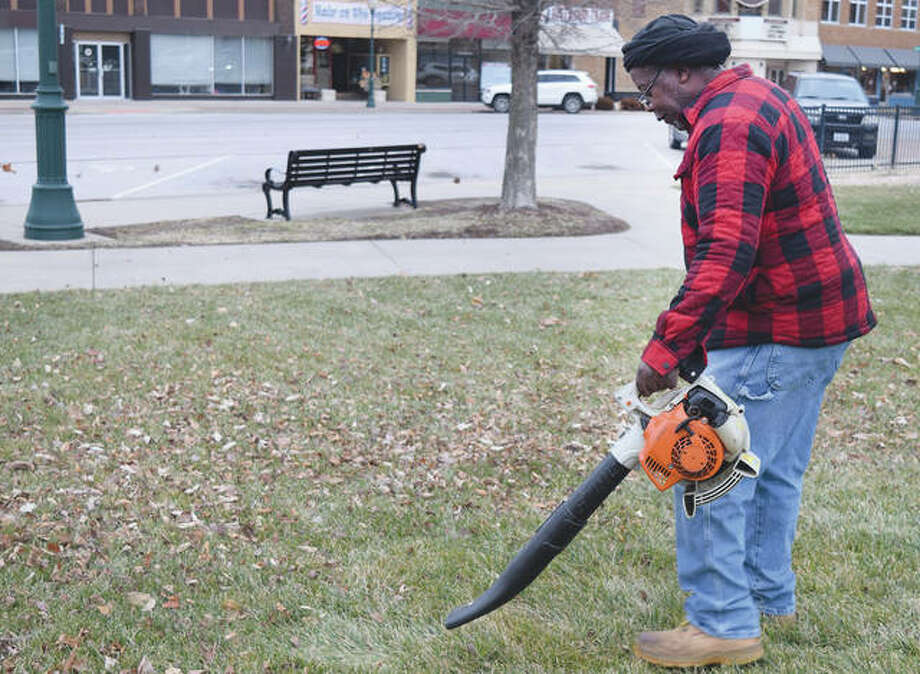 Bill Mayes, a maintenance worker for the city of Jacksonville, struggles against blustery winds Thursday to remove leaves from the downtown square. Gusts of 40 mph were recorded Thursday and could continue into part of today.