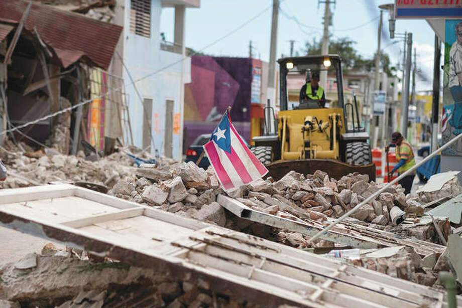 A Puerto Rican flag waves on top of a pile of rubble as debris is removed from a main road in Guanica, Puerto Rico, a day after an earthquake. Puerto Rico's governor declared a state of emergency after a powerful 6.4-magnitude quake killed at least one person and caused widespread damage. Photo: Ricardo Arduengo | AFP Via Getty Images