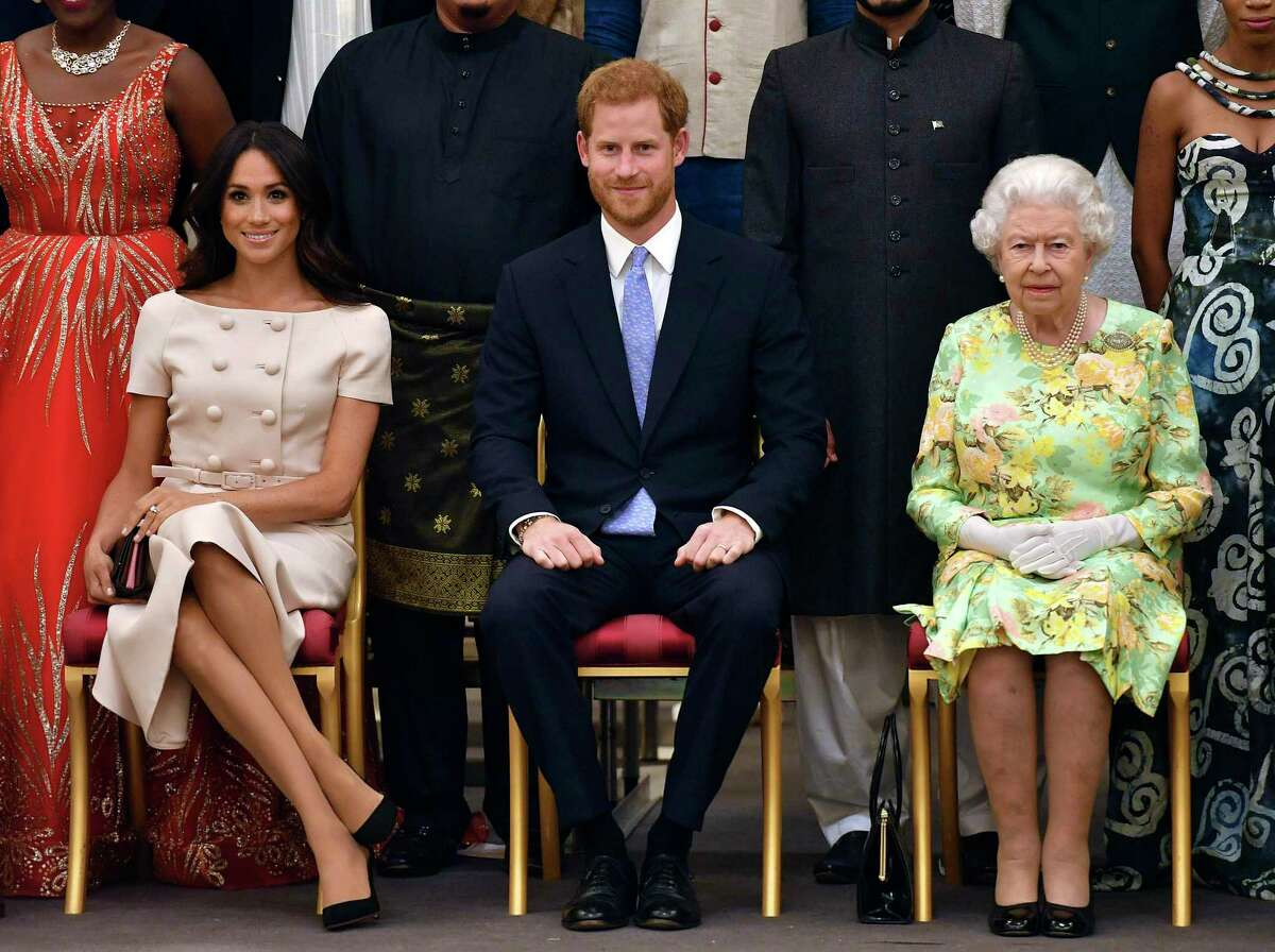 In this Tuesday, June 26, 2018 file photo, Britain's Queen Elizabeth, Prince Harry and Meghan, Duchess of Sussex pose for a group photo at the Queen's Young Leaders Awards Ceremony at Buckingham Palace in London. As part of a surprise announcement distancing themselves from the British royal family, Prince Harry and his wife Meghan declared they will