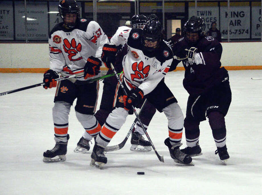 Edwardsville's Will Schuster, middle, controls the puck as teammate Justin Harper looks on during Thursday's game against Rockwood Summit at the East Alton Ice Arena. Photo: Scott Marion/The Intelligencer