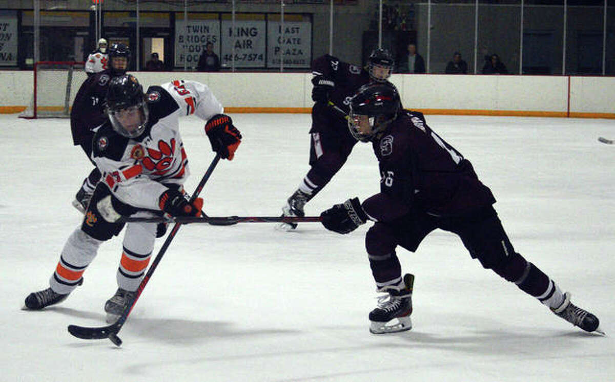 Edwardsville's Collin Salter, left, tries to get past a Rockwood Summit defender during Thursday's game at the East Alton Ice Arena.