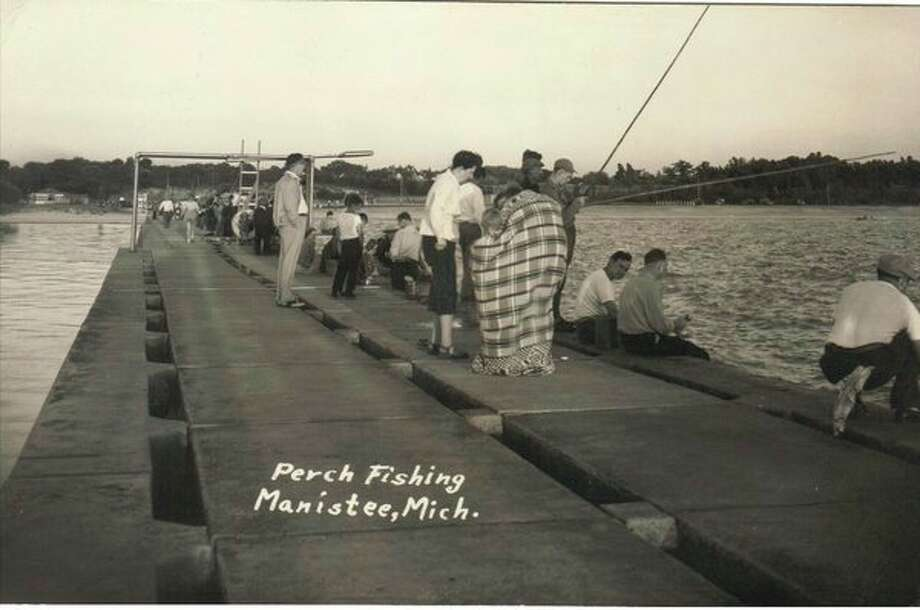 Perch fishing off the piers in Manistee was a popular activity in the early 1950s that drew in many people.