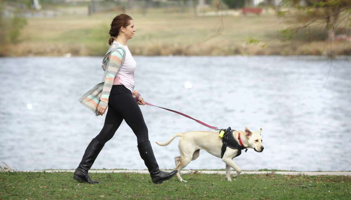 Alina Kaliuzhna, who was honorably discharged from the U.S. Army one year short of her contract, walks her dog Ivy, a 2 year-old rescue, at Woodlawn Lake.