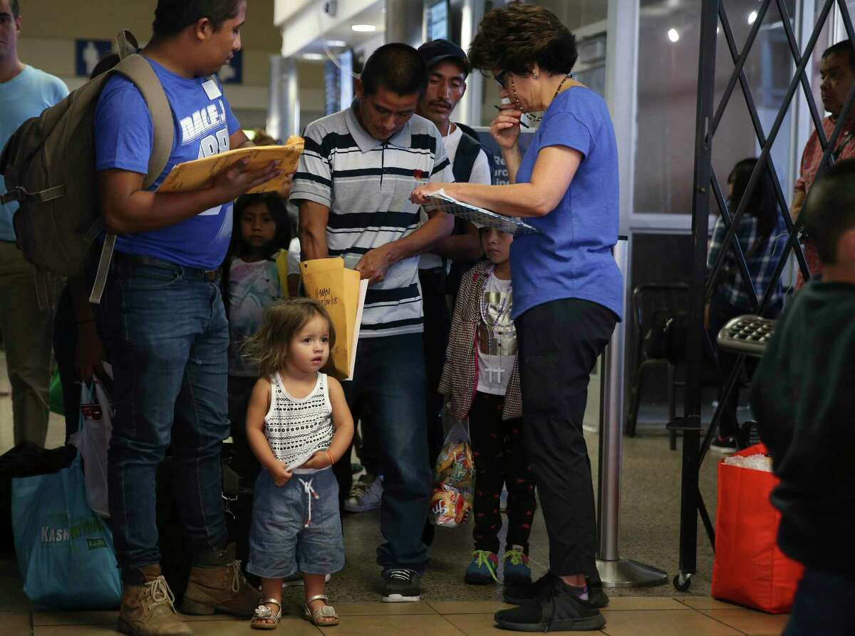 Honduran Brian Giron, 24, and his daughter Juliet are assisted by Interfaith Welcome Coalition volunteer Carolina Barrera at the Greyhound bus station.