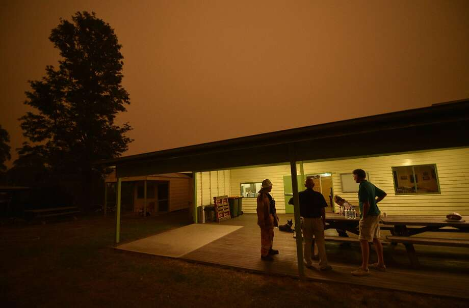 People gather at a community hall in Towamba in southern New South Wales state as the sky turns orange from wildfires burning near the town. Photo: Peter Parks / AFP Via Getty Images