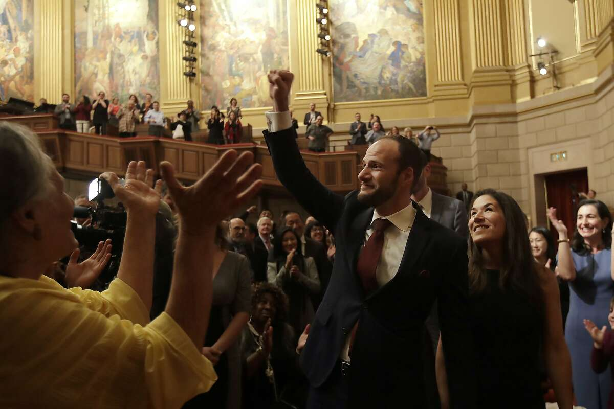 San Francisco District Attorney Chesa Boudin, center, gestures as he walks with Valerie Block during his swearing in ceremony in San Francisco, Wednesday, Jan. 8, 2020. (AP Photo/Jeff Chiu)