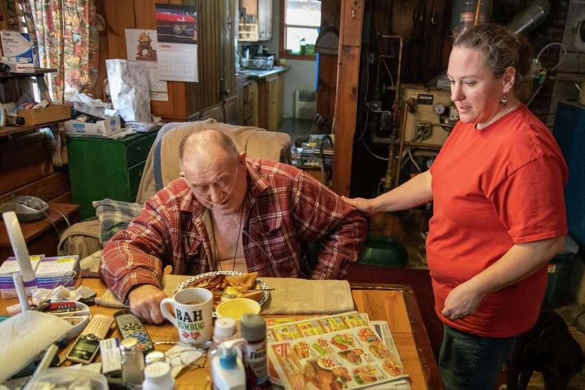 Home health aide Lisia Colegrove serves breakfast to client Thomas Wells.
