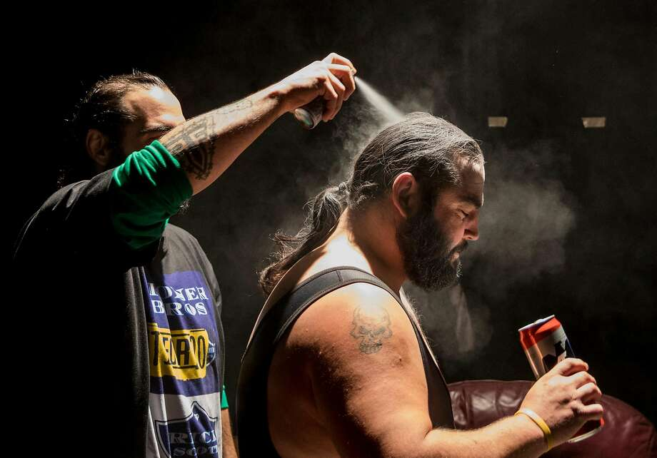 The Stoner Brothers help each other get ready for their wrestling match before the start of an 80's-themed Hoodslam event at Oakland Metro Operahouse in Oakland, Calif. Friday, Nov. 29, 2019. Photo: Jessica Christian / The Chronicle 2019