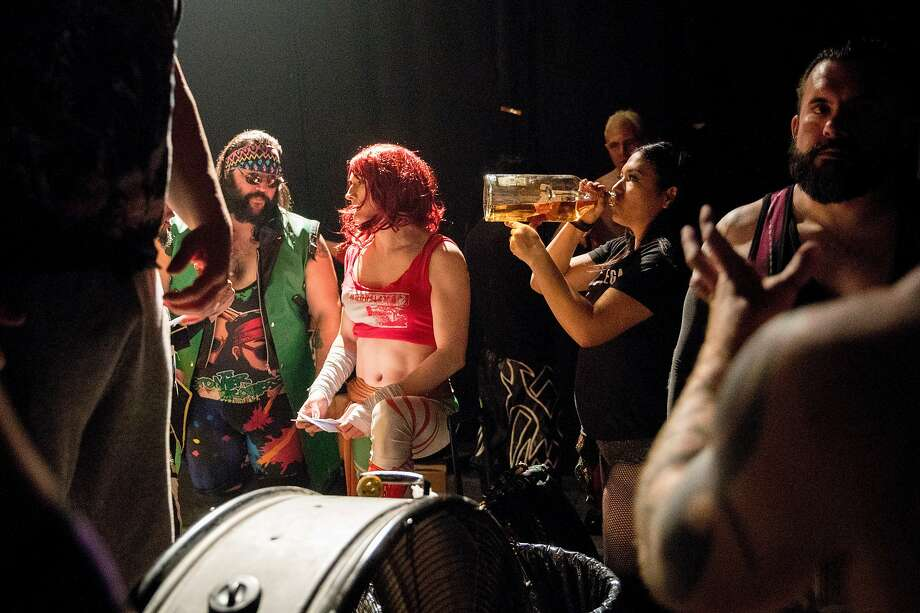 Sam Khandaghabadi (second left), known in the ring as Dark Sheik, chats with fellow wrestlers backstage while handing out paychecks before the start of a Hoodslam event at Oakland Metro Operahouse in Oakland, Calif. Friday, Jan. 3, 2020. Photo: Jessica Christian / The Chronicle