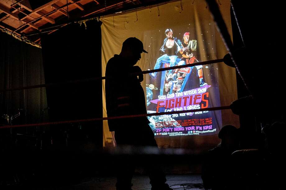 The ring is cast in shadow against a projected poster before the start of an 80's-themed Hoodslam event at Oakland Metro Operahouse in Oakland, Calif. Friday, Nov. 29, 2019. Photo: Jessica Christian / The Chronicle 2019