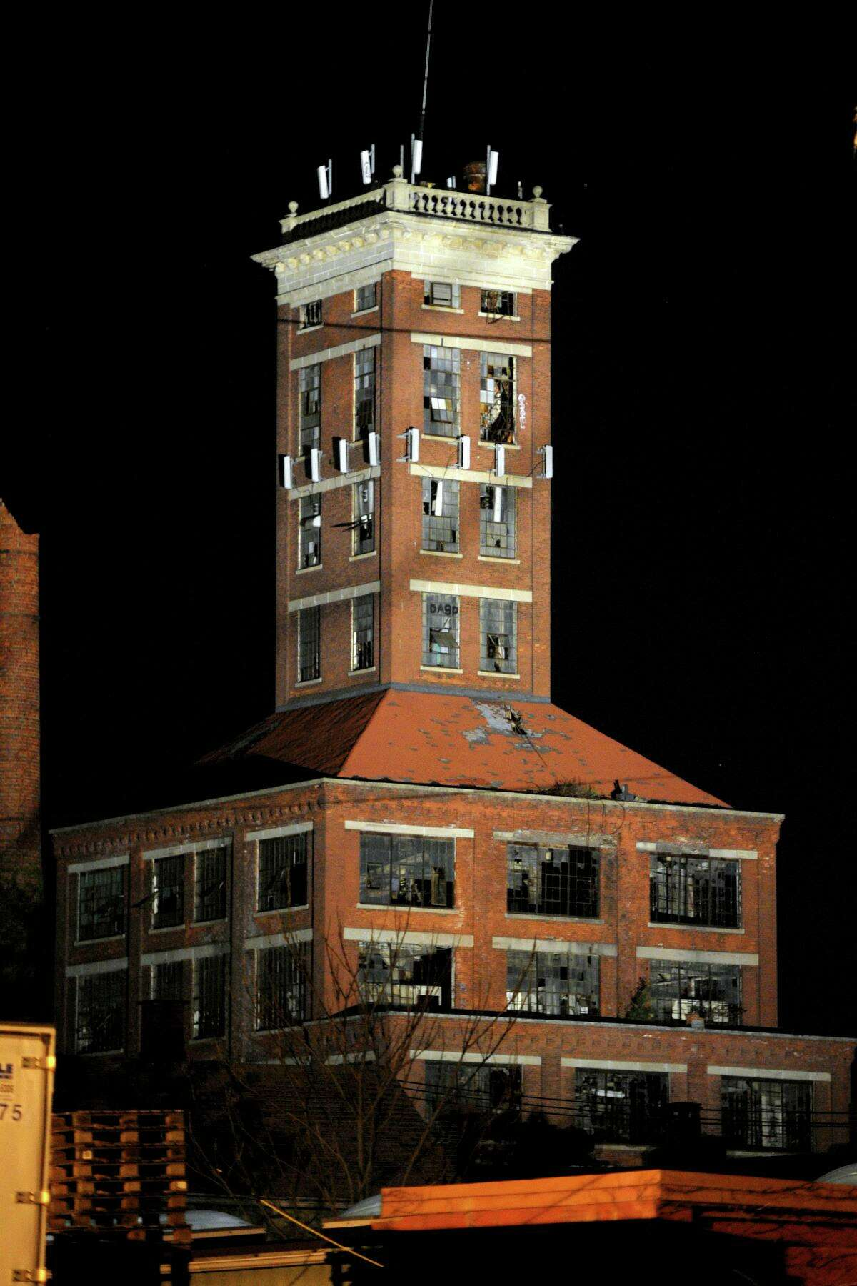 The ruins of the Remington Arms shot tower, built in 1909, stands lit by spotlights Saturday evening in Bridgeport, Conn. Oct. 5, 2019. The lighting event was staged by Colorblends Wholesale Flowerbulbs, who's warehouse is adjacent to the old Remington property in Bridgeport's east side.