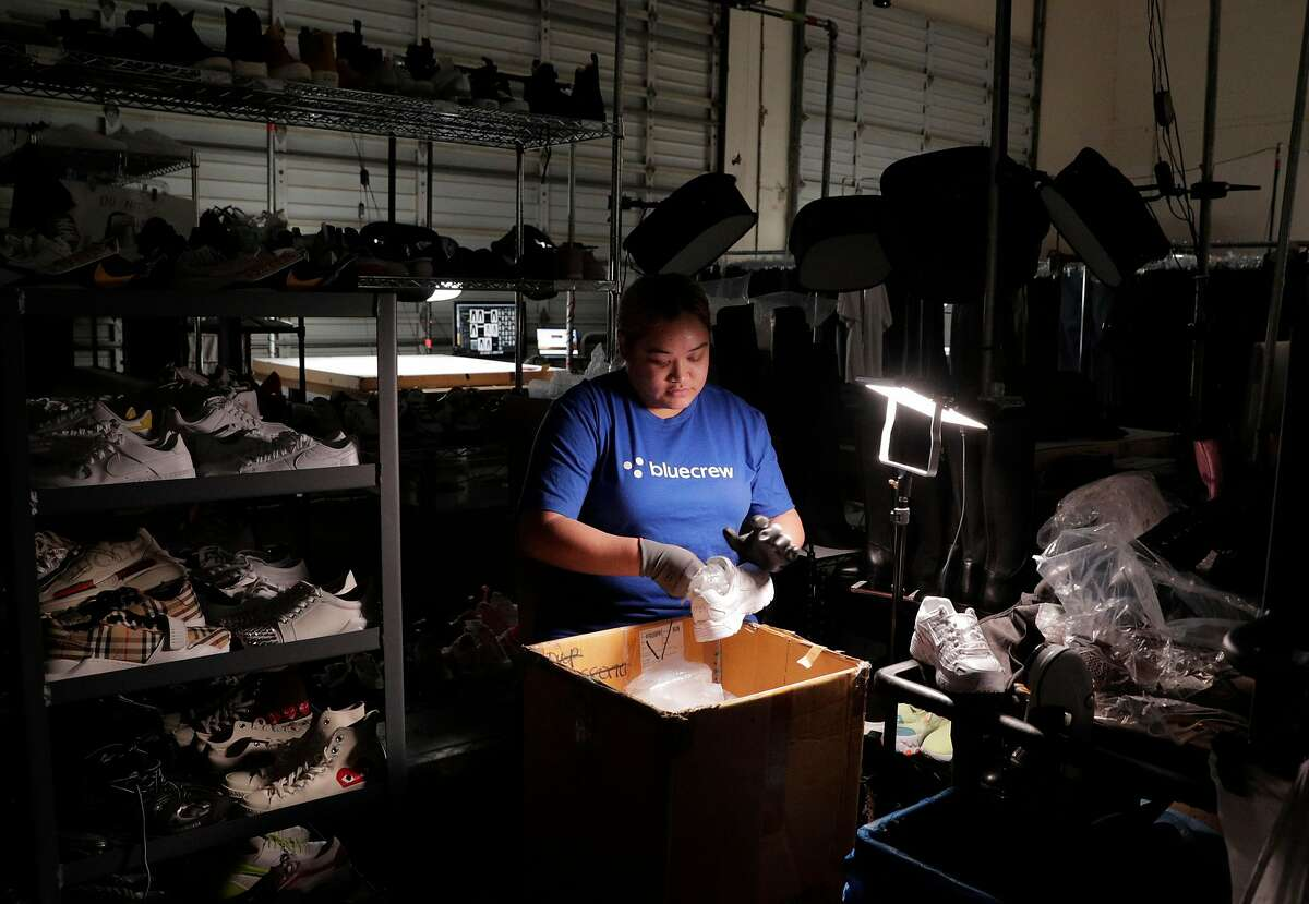 Crystal Yn preps footwear for photographs to be listed at the Yerdle warehouse where employees of BlueCrew have been hired by the company to assist in the company�s day to day operation in Brisbane, Calif., on Tuesday, January 7, 2020. BlueCrew has always hired its workers as employees, not independent contractors, so with Calif's new gig work law, it's getting many more inquiries from potential customers since it already complies with the new law.
