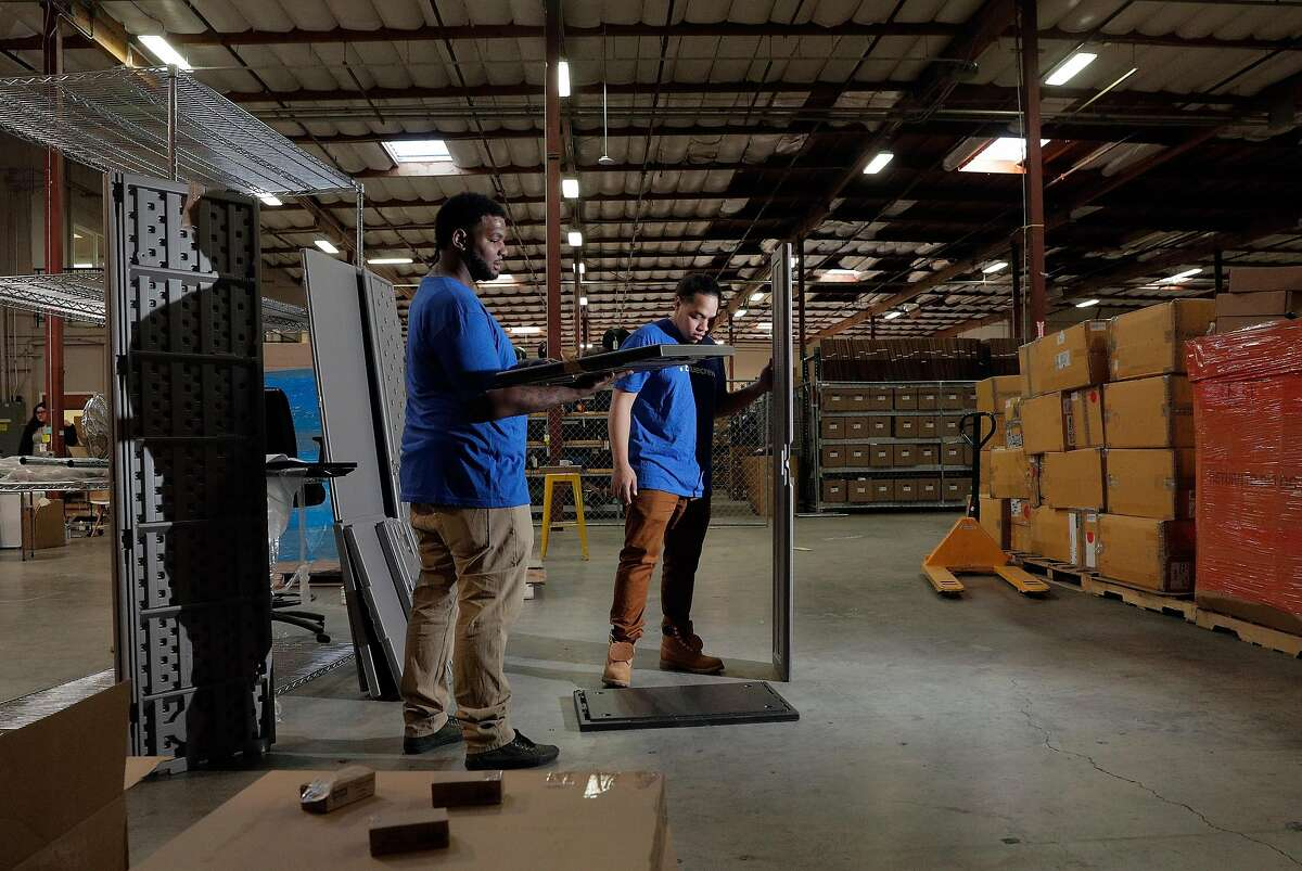 Nick Shelby, left, and Sekema Manuele, right, assemble a storage cabinet at the Yerdle warehouse where employees of BlueCrew have been hired by the company to assist in the company�s day to day operation in Brisbane, Calif., on Tuesday, January 7, 2020. BlueCrew has always hired its workers as employees, not independent contractors, so with Calif's new gig work law, it's getting many more inquiries from potential customers since it already complies with the new law.