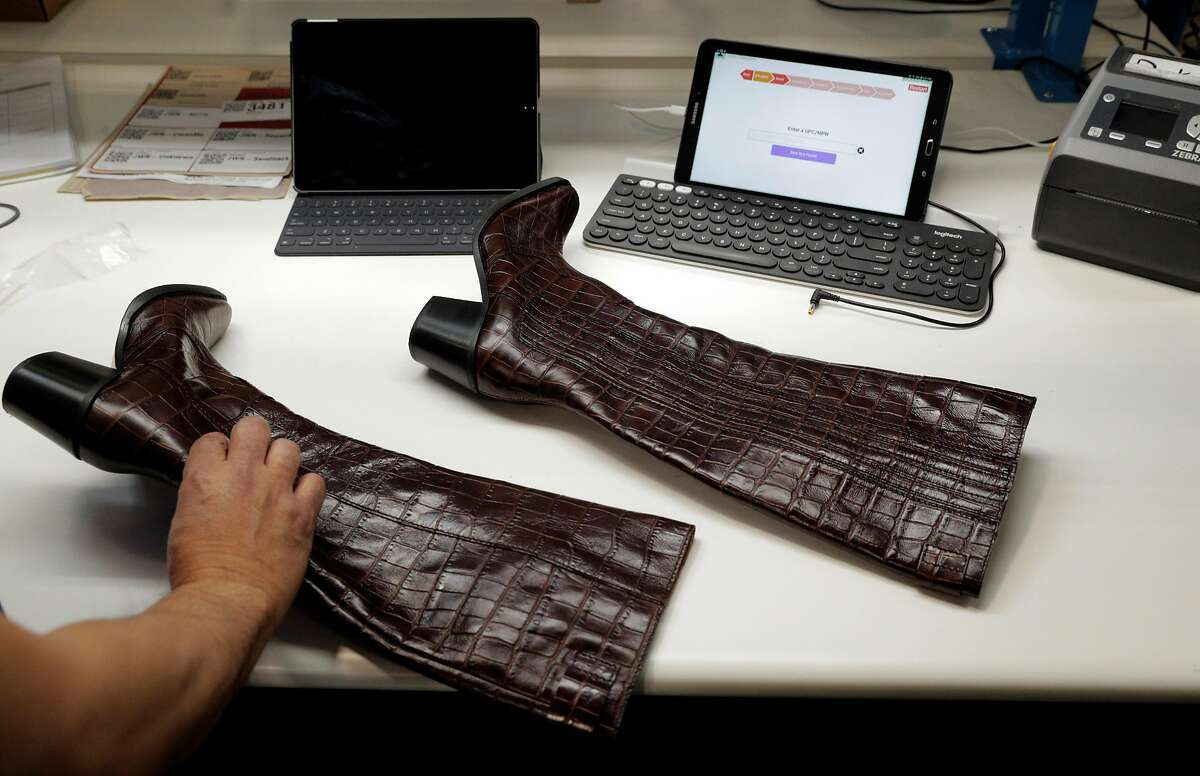 Robin Malau inspects a pair of Ganni Croc embossed knee-high leather boots at the Yerdle warehouse in Brisbane.
