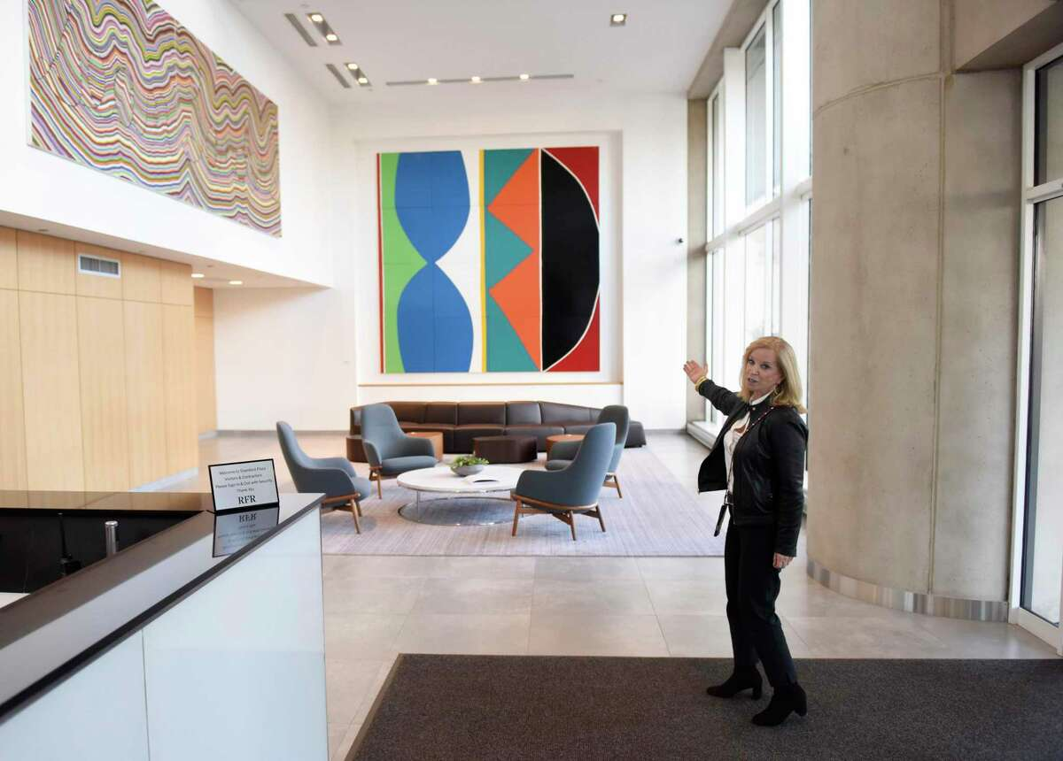 RFR Realty's Stamford portfolio director Margaret Carlson shows the lobby at 3 Stamford Plaza on Tresser Boulevard in Stamford, Conn., on Thursday, Jan. 9, 2020. The lobby includes a commissioned painting by Kim MacConnel, right, and another piece by Sean Landers. Office-building owners like RFR Realty see major renovations as critical to keeping and attracting tenants in a local market still saddled with many vacancies.