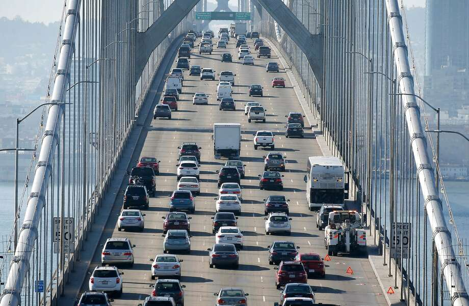 Westbound traffic slows to a crawl Friday past a tour bus stalled in the right lane of the Bay Bridge. Photo: Paul Chinn / The Chronicle